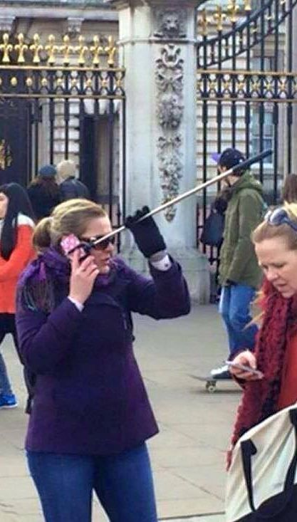Woman outside Buckingham Palace answers smartphone while it's hooked up to selfie stick