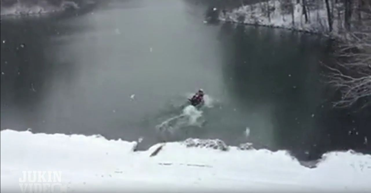 Canadians bobsleigh their canoe down a snowy hill into a freezing lake
