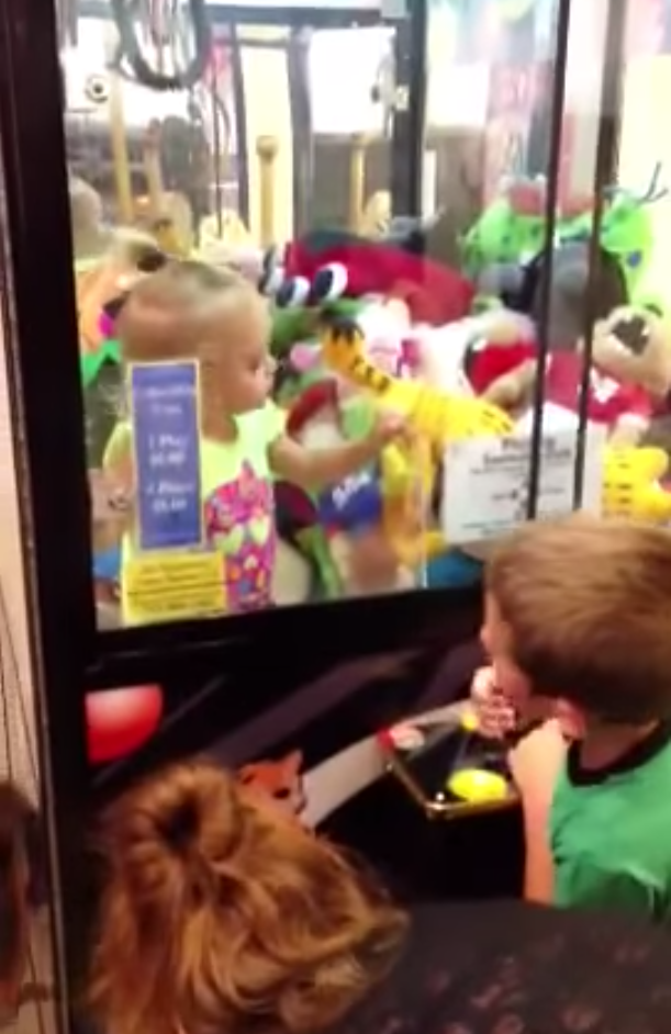 Little girl gets stuck in a claw machine, quickly followed by her sister