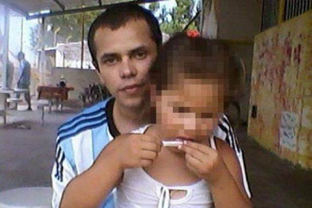 Prisoner poses with young daughter while she appears to roll him a spliff