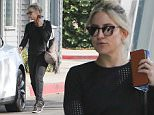 Kate Hudson fits in a workout wearing black sweats and mesh top